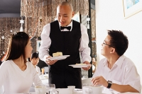 Couple in restaurant, waiter standing, holding plates of dessert - Asia Images Group