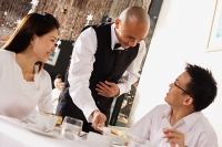 Waiter serving customers in restaurant - Asia Images Group