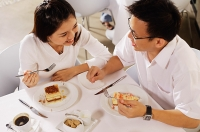 Couple eating dessert in restaurant, high angle view - Asia Images Group