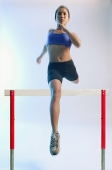 Woman running and jumping over hurdle - Asia Images Group