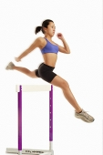 Woman jumping over hurdle - Asia Images Group
