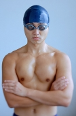 Man wearing swimming cap and goggles, arms crossed, looking at camera - Asia Images Group