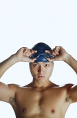 Man touching swimming goggles, looking at camera, portrait - Asia Images Group
