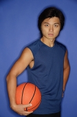 Man holding basketball under arm, looking at camera - Asia Images Group