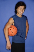 Man holding basketball under arm, looking at camera, smiling - Asia Images Group