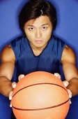 Man holding basketball out towards camera - Asia Images Group