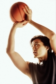 Man aiming basketball, looking away - Asia Images Group