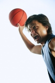 Man holding basketball in the air, mouth open - Asia Images Group