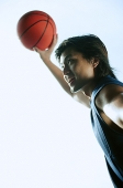Man holding basketball in the air, smiling - Asia Images Group