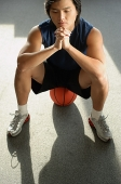 Man sitting on basketball - Asia Images Group