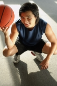 Man crouching, holding basketball, looking up at camera - Asia Images Group