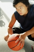 Man crouching, holding basketball, portrait - Asia Images Group