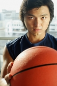 Man holding basketball, looking at camera - Asia Images Group
