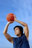 Man aiming basketball - Asia Images Group
