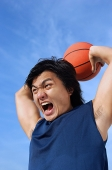 Man holding basketball, shouting - Asia Images Group