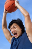 Man holding basketball up, shouting - Asia Images Group