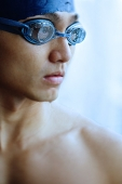 Man in swimming cap and goggles, looking away, portrait - Asia Images Group