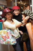 Women shopping, trying on hats, one woman adjusting hat for her friend - Asia Images Group