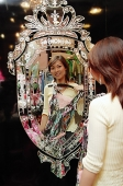 Woman in clothing store, holding dress, looking at mirror - Asia Images Group