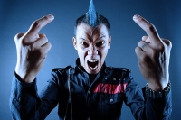 Man with mohawk, mouth open, making hand sign - Asia Images Group