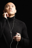 Man with shaved head, listening to music with earphones, portrait - Asia Images Group