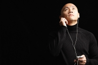 Man with shaved head, listening to music with earphones - Asia Images Group