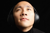 Man with shaved head, wearing headphones - Asia Images Group