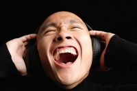 Man with shaved head, wearing headphones, mouth open - Asia Images Group