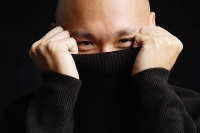 Man hiding behind turtleneck - Asia Images Group