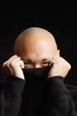 Man hiding behind turtleneck, looking at camera - Asia Images Group