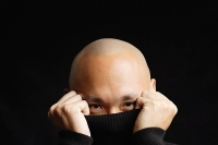 Man hiding behind turtleneck, obscured face - Asia Images Group