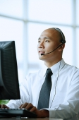 Man with headset, using computer - Asia Images Group