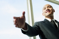 Businessman, hand outstretched, smiling - Asia Images Group