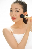 Woman applying blusher with make-up brush - Asia Images Group