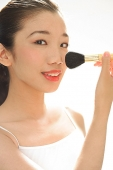 Woman holding make-up brush to face, looking at camera - Asia Images Group