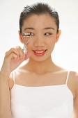 Woman holding eyelash curler, looking away - Asia Images Group