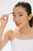 Woman holding brush to eyebrows - Asia Images Group