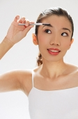 Woman brushing eyebrows - Asia Images Group