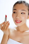 Woman looking at lipstick in her hand - Asia Images Group
