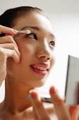 Woman applying eye shadow - Asia Images Group