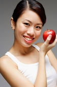 Woman holding apple, looking at camera - Asia Images Group