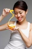 Woman holding orange and pulling orange peel - Asia Images Group