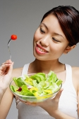 Woman looking at tomato on fork and holding bowl of salad - Asia Images Group