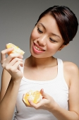 Woman holding peeled orange - Asia Images Group
