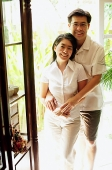 Couple standing in doorway, looking at camera - Asia Images Group