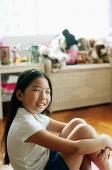 Girl in bedroom, sitting on floor, hugging knees, looking at camera - Asia Images Group