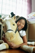 Girl in bedroom, hugging stuffed toy - Asia Images Group