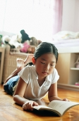 Girl in bedroom, lying on floor, reading book - Asia Images Group