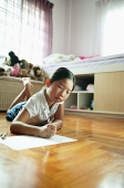 Girl in bedroom, lying on floor, drawing on paper - Asia Images Group