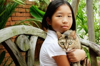 Girl holding cat, looking at camera - Asia Images Group